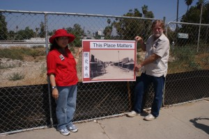 Image of Judy Lee with SOCC supporter with a sign at the Riverside, Calif. Chinatown historic site. 2009