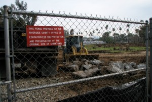 Image of the fence and earth-movers at the Riverside, California historic Chinatown archaeological site. 2009.