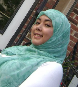 Image of Ariana Hussain, wearing a green headscarf and a white long-sleeved shirt.