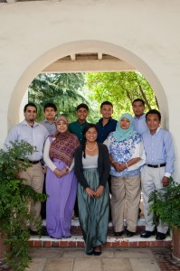 An image of Ariana Hussain, the article's author, in a family photo, consisting of nine individuals.