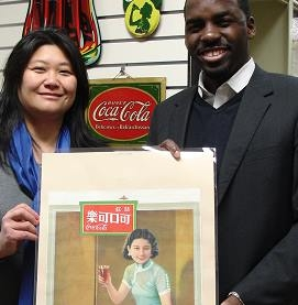 APALA member Tricia Sung (L) and Jamal Booker (R), Coca-Cola Company Archivist, at the Coca-Cola Company Archives, 2013. Both are holding up an advertising poster published in 1936 and used in American Chinatowns.