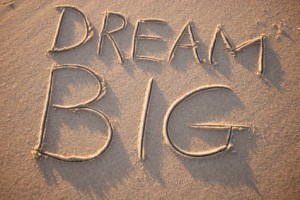 "Image with ""dream big"" written in the sand."